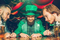 Greedy young man in green suit sit at table with friends and look at golden coins he grabbed. Other guys look at them. Greedy young men in green suit sit at stock images