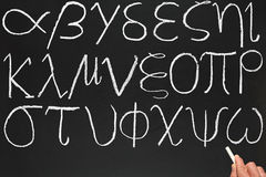Greek alphabet. A teacher writing the Greek alphabet on a blackboard Stock Images