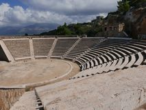 Greek Amphitheater in the Peloponnese. Stone Greek amphitheater on the Peloponnese with mountain background Royalty Free Stock Photos
