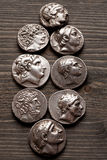 Greek ancient silver coins on a wooden table Stock Photo