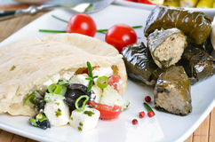 Greek appetizers. Cold Greek appetizers: stuffed flat bread, stuffed vine leaves, sheep's milk cheese, olives Royalty Free Stock Photo