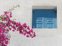 Greek architecture. Details of traditional Greek island architecture - window with blue painted shutters on white wall and purple Bougainvillea blossom Stock Image