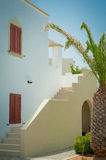 Greek architecture - white buildings, sea and blue windows, tree Stock Photos