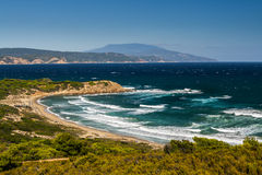 Greek bay with a sand beach. Big waves wash a small beach in a bay royalty free stock image