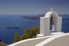 Greek bell tower. With caldera and cruise ship against a clear blue sky Stock Photo