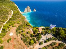 Greek biggest national flag waving in the sky in Keri in Zakynth. Os Zante island in Greece Royalty Free Stock Photo