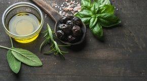 Greek black olives, fresh herbs and oil on dark rustic wooden background. Greek black olives, fresh green sage, rosemary, basil herbs, salt and oil on dark royalty free stock photo