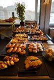 Greek breakfast buffet table full with varieties of pastries, buns, pancakes, donuts, butter cake, pizza, pies, boiled eggs, etc. Stock Photo
