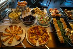 Greek breakfast buffet table full with varieties of pizza, pies, pasta, beetroot, couscous salads, boiled eggs, local dishes, etc. Stock Images