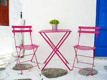 Greek Breakfast table and chairs. A pink coloured breakfast table and chairs on the streets of Mykonos Greek Island Stock Photo
