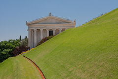 Greek building behind green grass slope, Bahai gardens, Israel Royalty Free Stock Photography