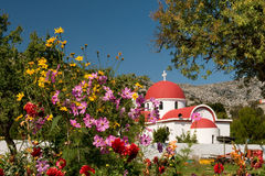 Greek catholic church in Crete. Together with flowers and clear blue sky Stock Image