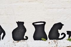 Greek cats painted on the wall of a fence. The feline friends are all over Greece just waiting to snap up a tid-bit under the taverna table or find a shady spot Stock Photos