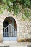 Greek chapel. Stone, iron lattice, cross. Inscription in Greek language stock image
