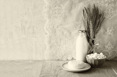 Greek cheese , bulgarian cheese and milk on wooden table over wooden textured background. black and white photo.  Symbols of jewis Stock Photos