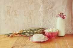 Greek cheese , bulgarian cheese and milk on wooden table over wooden textured background. Symbols of jewish holiday - Shavuot Stock Image