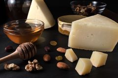 Greek cheese graviera and a slices on black stone board. With nuts, honey and herbs Stock Image