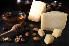 Greek cheese graviera and a slices on black stone board with nuts. Honey and herbs Royalty Free Stock Photography