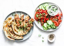 Greek chicken skewers, flatbread, tomatoes, cucumber salad, baked sweet pepper, tzatziki yogurt herb sauce on a light background,. Top. Mediterranean style stock image