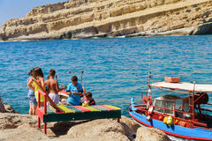 Greek children are catching fish at coast of Matala town on Crete island, Greece Stock Photos