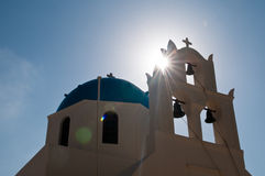Greek church. In Santorini island, Greece. Photo was taken against the sun to show the sun ray and flare Stock Image
