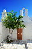 Typical white Greek church. Village square. Greek church, typical white Aegean island architecture. Village square with orange tree in Paros, Greece royalty free stock photo