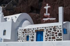 Greek church with red rock behind. Santorini, Greece. Red beach. Europe Royalty Free Stock Photography