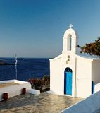 Greek church and sea. View of a traditional white Greek church and blue sea Stock Photography