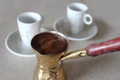 Greek coffee in briki with two cups. Greek coffee also known as Turkish coffee, made in briki.  A briki is a small sort of pot used to boil Greek or Turkish Royalty Free Stock Photo