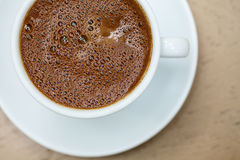 Greek coffee cup close-up. Top view of white cup with frothy greek coffee on a wooden table Stock Photos