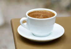 Greek coffee cup close-up. White cup with frothy greek coffee on a cafe table Royalty Free Stock Image