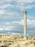 Greek column. Greek corinthian column and ancient ruins against the blue sky with clouds. Copy space on the left Stock Images