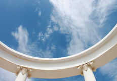 Greek columns tend to sky. With white clouds Royalty Free Stock Photography