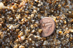 Greek copper coin in sea sand. Old greek copper coin in sea sand royalty free stock image