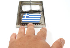 Greek crisis trap. A mousetrap clatters with a flag and a hand reaching for it Royalty Free Stock Photo