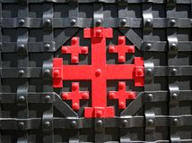 Greek cross in red on an iron gate. The `Jerusalem cross` is the symbol of the Custody of the Holy Land. Greek cross in red on an iron gate. Jerusalem cross is Royalty Free Stock Photography