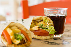 Greek cuisine, souvlaki. Gyro pita. and a glass of drink. In the tavern in Greece Royalty Free Stock Photo