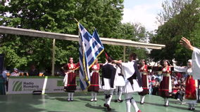 Greek dance. Group of men and women dancing popular Greek dance with Romanian and Greek flags stock video