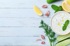 Greek dip sauce or dressing tzatziki from sour cream yogurt decorated with olive oil and mint on wooden table top view. Royalty Free Stock Photo
