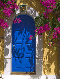 Blue door in greece with purple flower Royalty Free Stock Image