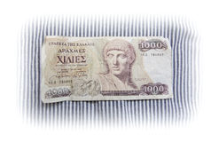 Greek drachma paper currency. Banknote printed in 1987 in the amount of 1000.- greek drachma against blue and white striped fabrics with faded edges. No longer Stock Image