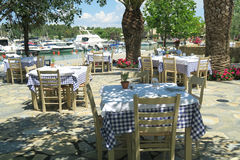 Greek empty taverna chairs and tables by a marina in Greece. A greek tavern by the marina on a summer day at a resort in Halkidiki, Greece stock photos