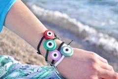 Greek evil eye bracelets advertisement on beach Stock Image