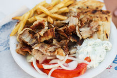Greek Fast Food. Greek tasty fast food, gyros and fried potato , tomato and onion Stock Photography