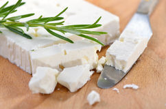 Greek feta. Typical Greek feta cheese made of goat milk, served with rosemary, wooden cutting board Stock Photo