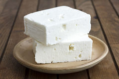 Greek feta cheese block on rustic plate and table. Stock Photos