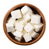 Greek Feta cheese cubes in wooden bowl over white Stock Image