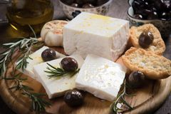 Greek feta cheese. Famous dairy product with black olives and rosemary Stock Images