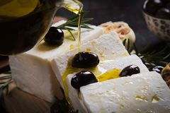 Greek feta cheese. Famous dairy product with black olives and rosemary Royalty Free Stock Image