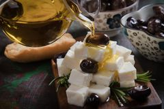 Greek feta cheese. Famous dairy product with black olives and rosemary Royalty Free Stock Images
